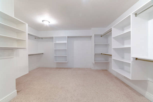 Empty white shelves in a fitted walk-in wardrobe stock photo