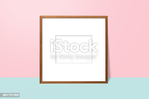 istock empty white space in wooden blank frame leaning against with pink wall and blue floor. simple blank photo frame for presentation or decorate background 984791958