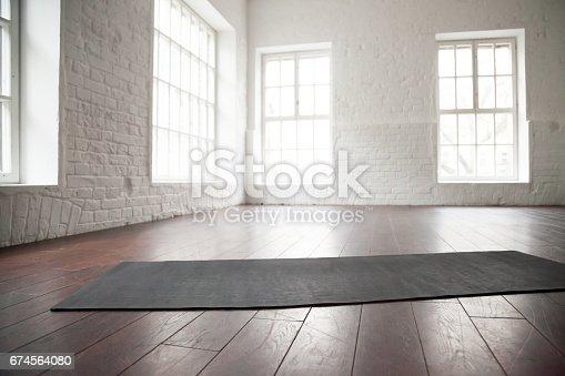 istock Empty white space, loft studio, yoga mat on the floor 674564080