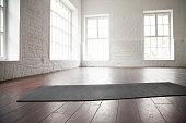 Empty white space, loft studio, yoga mat on the floor
