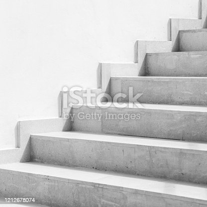 Empty gray stone stairway near white wall, abstract architectural background, square black and white photo
