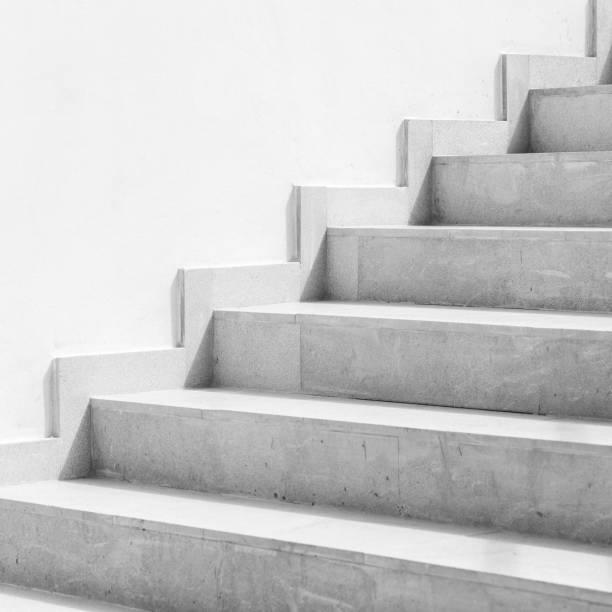 leere weiße steintreppe in der nähe der weißen wand - treppe stock-fotos und bilder