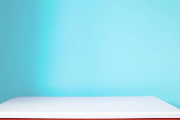 mesa blanca vacía y pared azul en la guardería - foto de stock