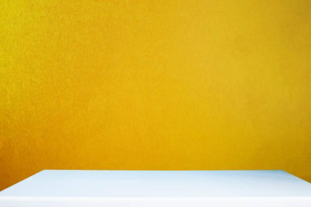 mesa blanca vacía y pared dorada en la habitación - foto de stock