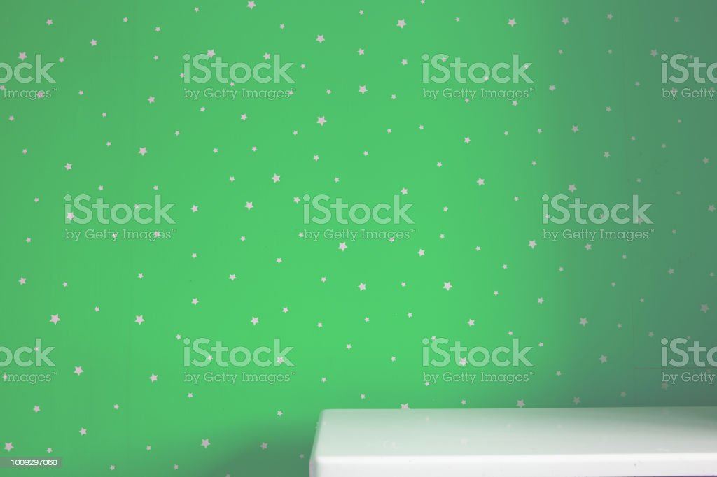 Empty white table and green starry wall stock photo