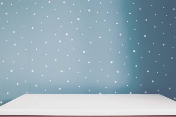 Mesa blanca vacía y gris suave azul estrellado pared de habitación de los niños. - foto de stock