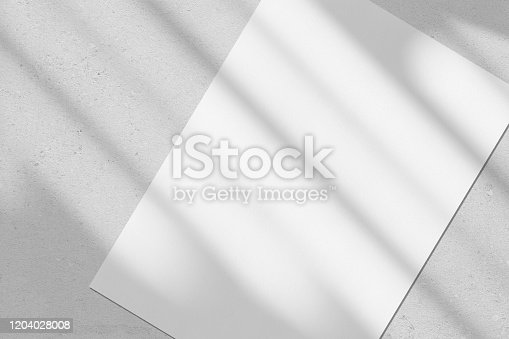 istock Empty white vertical rectangle poster mockup with diagonal window shadow on the wall 1204028008