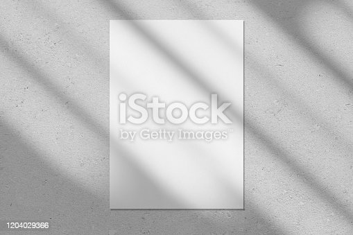 istock Empty white vertical rectangle poster mockup with diagonal window shadow on the wall 1204029366