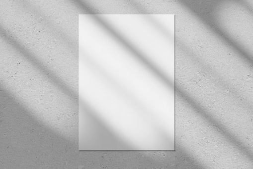 Empty white vertical rectangle poster or business card mockup with diagonal window shadow on the smooth gray concrete wall.Flat lay, top view. For advertising, brand design, stationery presentation.