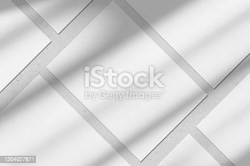 istock Empty white vertical rectangle poster mockups with diagonal window shadow on the wall 1204027871
