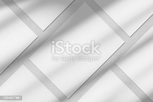 istock Empty white vertical rectangle poster mockups with diagonal window shadow on the wall 1204027981