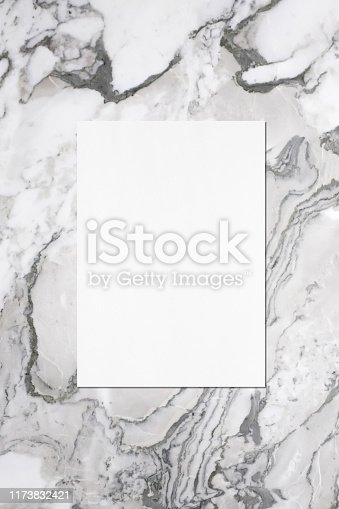 istock Empty white vertical rectangle poster or business card mockup with soft shadow on grey marble background 1173832421