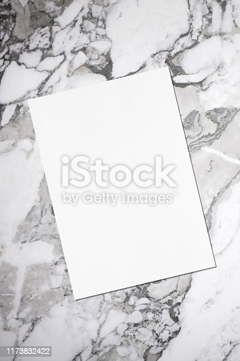 istock Empty white vertical rectangle poster or business card mockup with soft shadow lying diagonally on grey marble background 1173832422