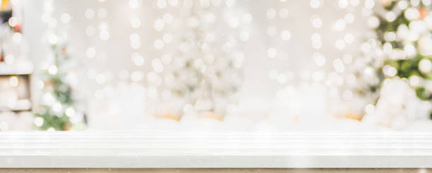 empty white wold table top with abstract warm living room decor with christmas tree string light blur background with snow,holiday backdrop,mock up banner for display of advertise product. - christmas table foto e immagini stock