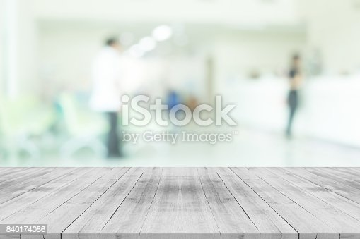 836113142 istock photo Empty white wood table top on blur hospital interior for background,space for montage products 840174086