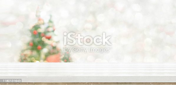 530427918 istock photo Empty white wood table top with abstract warm living room decor with christmas tree string light blur background with snow,Holiday backdrop,Mock up banner for display of advertise product 1180131643