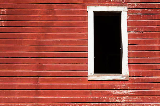 Empty window frame against red wall with blank space stock photo