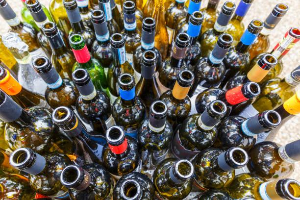 leere weinflaschen nach einer party - recycelte weinflaschen stock-fotos und bilder