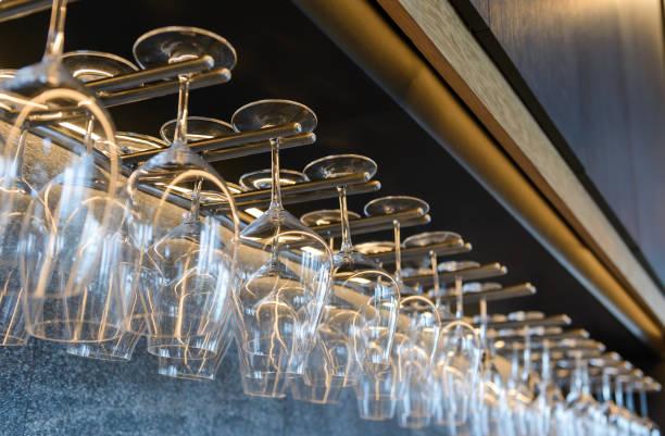 leere Weingläser hängen auf Regal in Bar – Foto