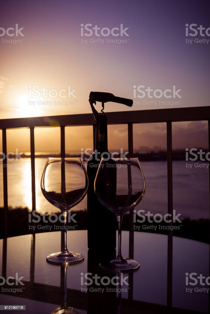 Empty wine glasses and bottle on balcony overlooking at sunset