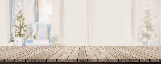 Empty wold plank table top with abstract warm living room decor with christmas tree blur background with bokeh light,Holiday backdrop,Mock up banner for display of advertise product ,luxury house stock photo