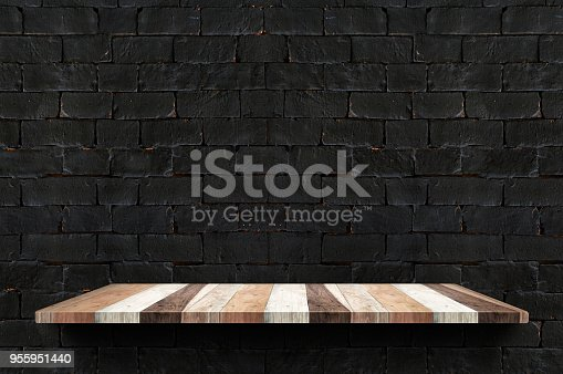 593305530istockphoto Empty wood board shelf at black brick wall background,Mock up for display or montage of product or design 955951440