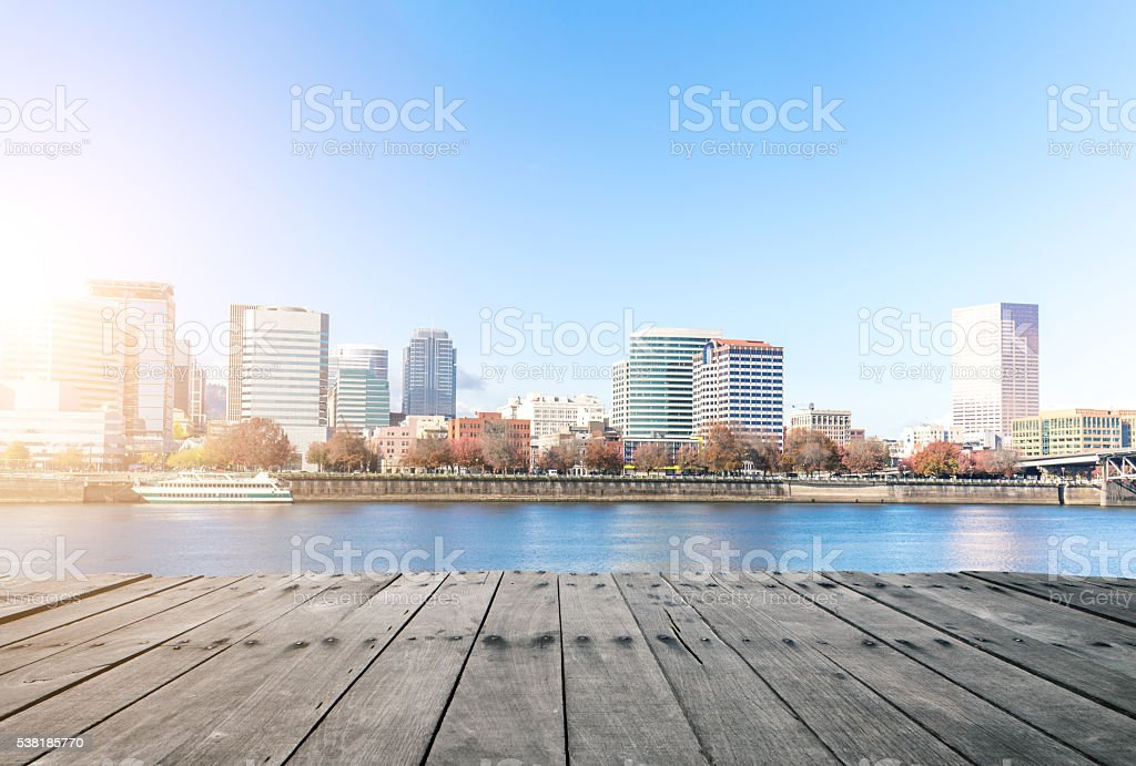 empty wood floor near water with cityscape and skyline stock photo