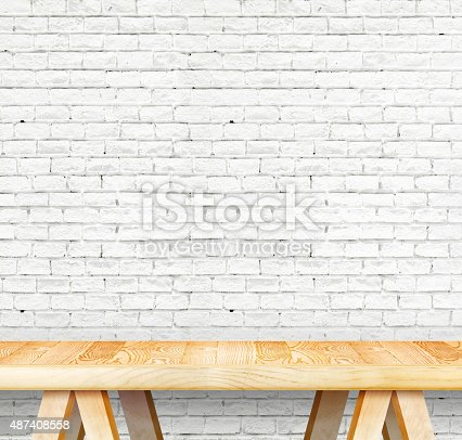 593305530istockphoto Empty wood modern table and grunge white brick wall 487408558