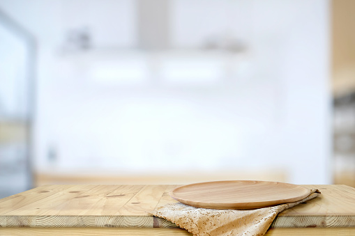 Empty Wood plate on wooded  table with modern kitchen accessories, for food and product display montage
