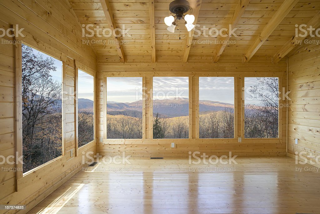 Empty wood room with several windows looking out to mountain royalty-free stock photo