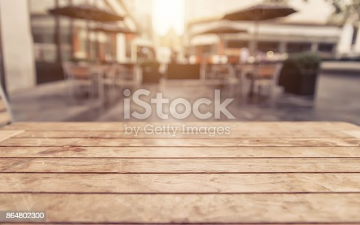 istock Empty wood table and blurred cafe with bokeh light background 864802300