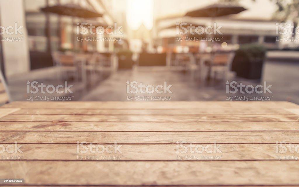 Leere Holztisch und verschwommene Café mit bokeh hellen Hintergrund – Foto