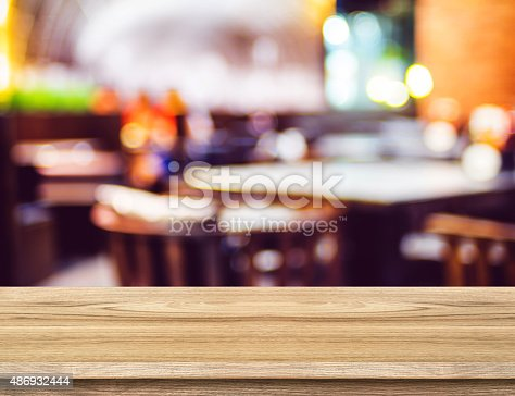 862429776 istock photo Empty wood table and blurred restaurant background. product disp 486932444