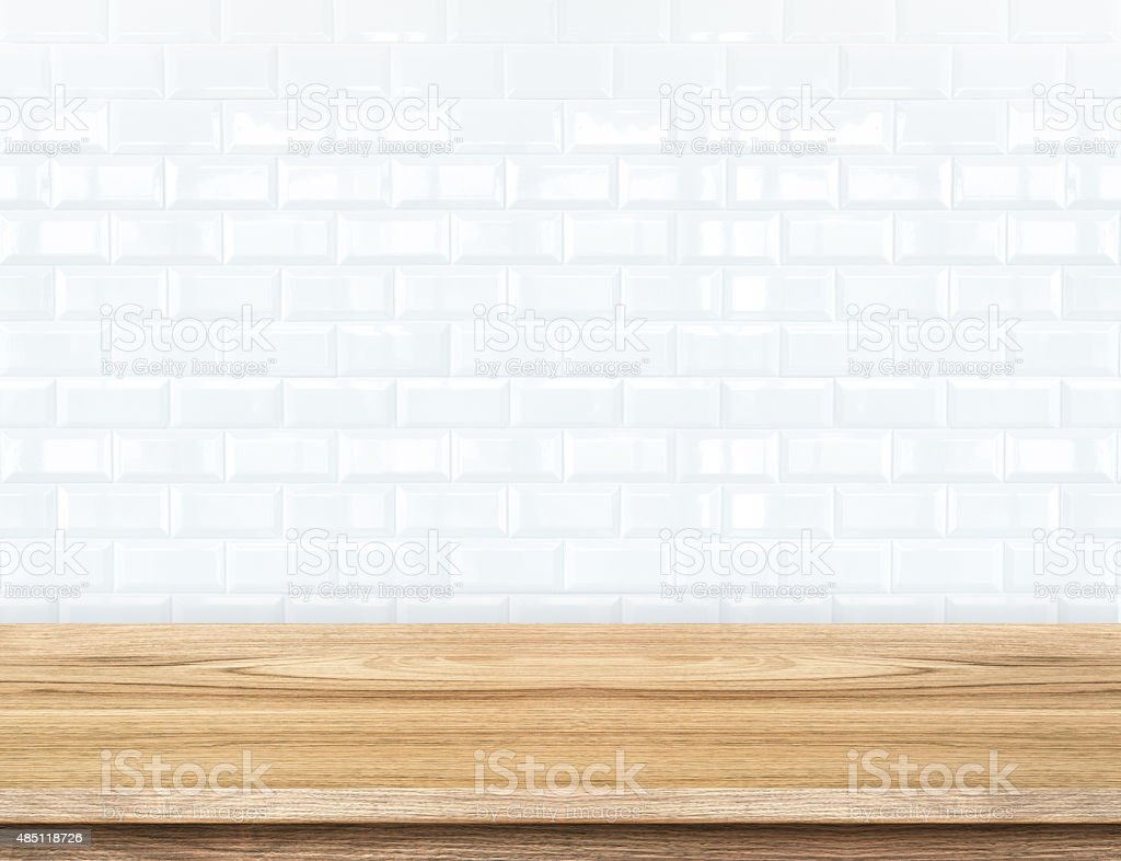 Empty wood table and ceramic tile brick wall in background stock photo