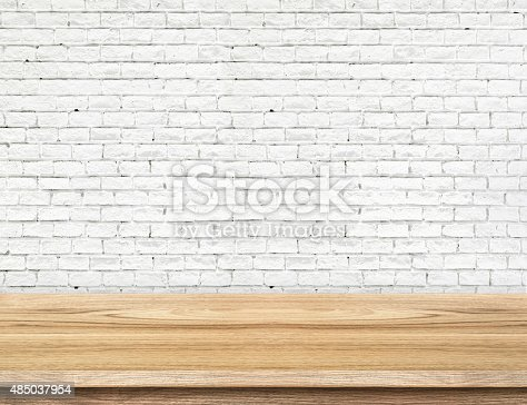 593305530istockphoto Empty wood table and white brick wall in background 485037954