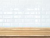 Empty wood table and  white ceramic tile brick wall
