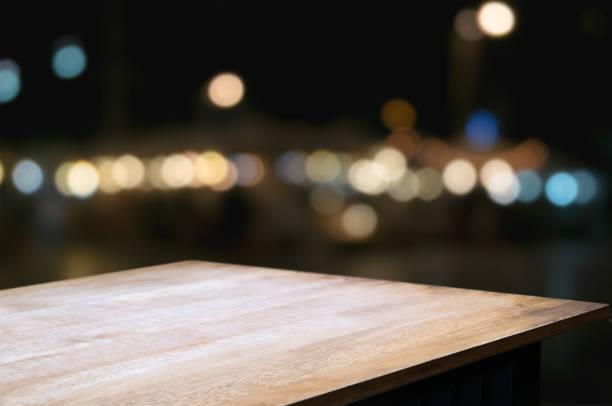 mesa de madera vacía frente a fondo de borrosa montaje nocturno mercado bokeh - perspectiva fotografías e imágenes de stock