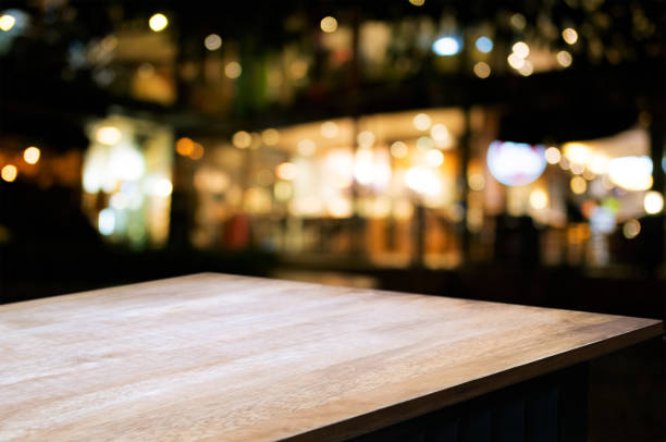 empty wood table in front of blurred montage night market bokeh background stock photo