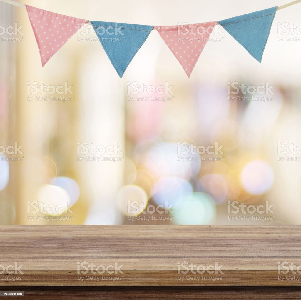 Empty wood table over colorful party flags and blur bokeh background, new year, christmas, festival background, banner - fotografia de stock