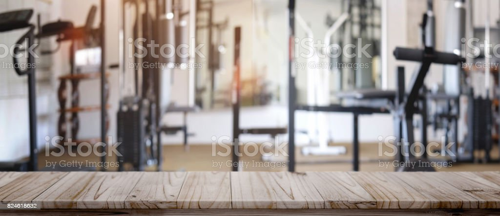 Empty wood table space platform and fitness gym background. stock photo