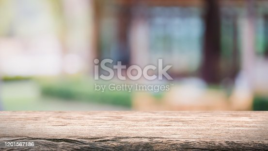 662984808 istock photo Empty wood table top and blur glass window exterior outdoor restaurant banner mock up abstract background - can used for display or montage your products. 1201567186