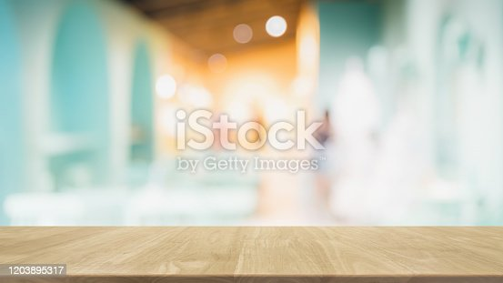 662984808 istock photo Empty wood table top and blur glass window interior restaurant banner mock up abstract background - can used for display or montage your products. 1203895317