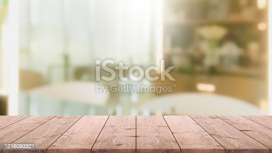 662984906 istock photo Empty wood table top and blur glass window interior restaurant banner mock up abstract background - can used for display or montage your products. 1216093321