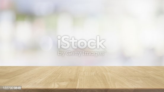 662984906 istock photo Empty wood table top and blur glass window interior restaurant banner mock up abstract background - can used for display or montage your products. 1227323848