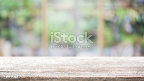 662984906 istock photo Empty wood table top and blur glass window interior restaurant banner mock up abstract background - can used for display or montage your products. 1227323886