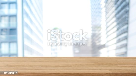 662984808 istock photo Empty wood table top and blur glass window wall building banner mock up background - can used for display or montage your products. 1154336847