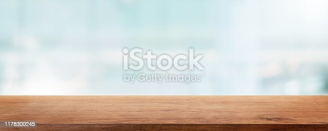 662984808 istock photo Empty wood table top and blur glass window wall building banner mock up abstract background - can used for display or montage your products. 1178300245