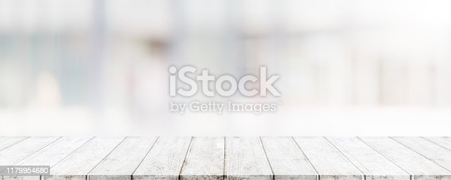 662984808 istock photo Empty wood table top and blur glass window wall building banner mock up abstract background - can used for display or montage your products. 1179954680