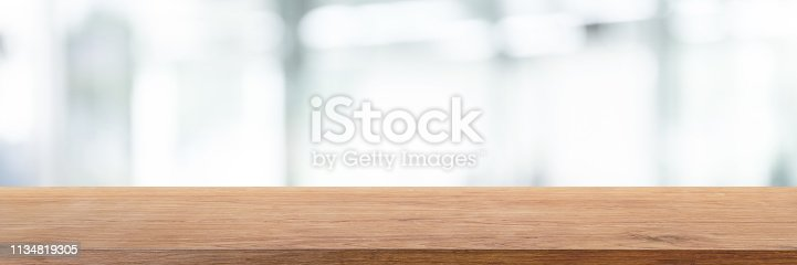 istock Empty wood table top and blur glass window wall in office building background - can used for display or montage your products. 1134819305