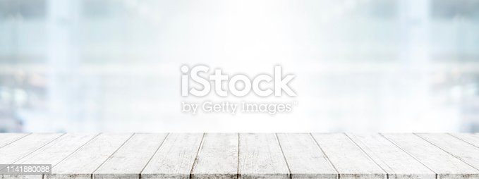 662984808 istock photo Empty wood table top and blur glass window wall in office building background - can used for display or montage your products. 1141880088